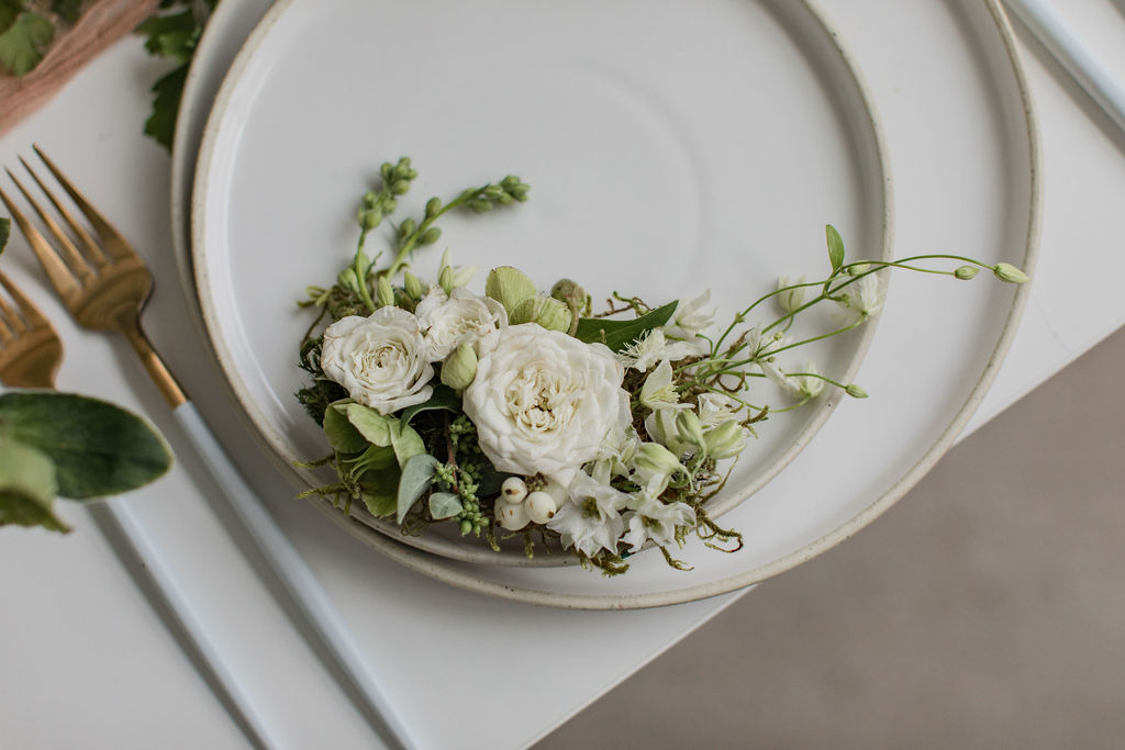 a floral hair piece sits on a white stoneware plate