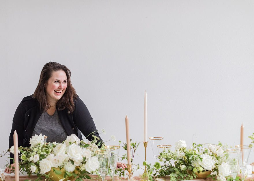 owner Carolyn Kulb looks over a table of white floral arrangements, neutral candles, and white and gold place settings