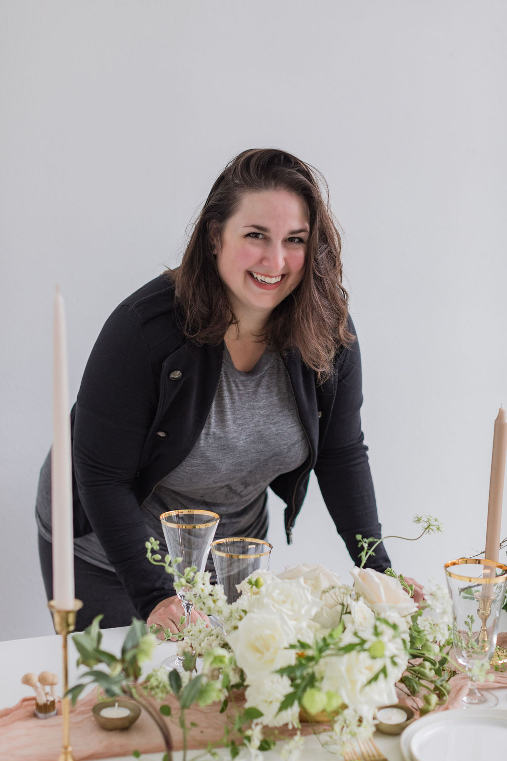 Folk Art Flowers owner Carolyn Kulb leans over a wedding table full of flowers, golden-rimmed glassware, and neutral candles