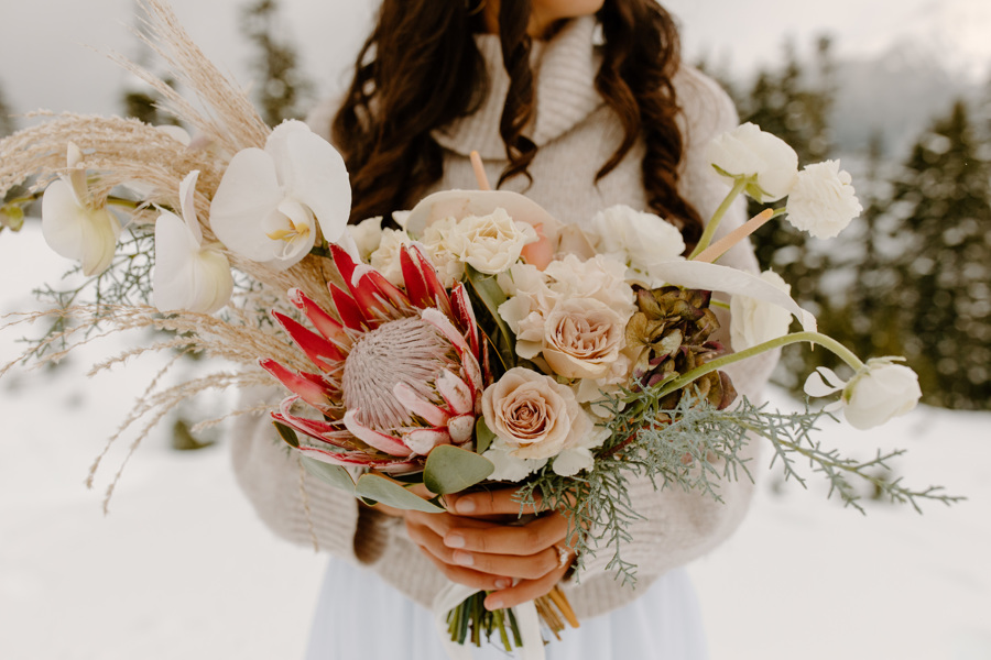 bride holding wedding bouquet in snowy Mt. Baker elopement