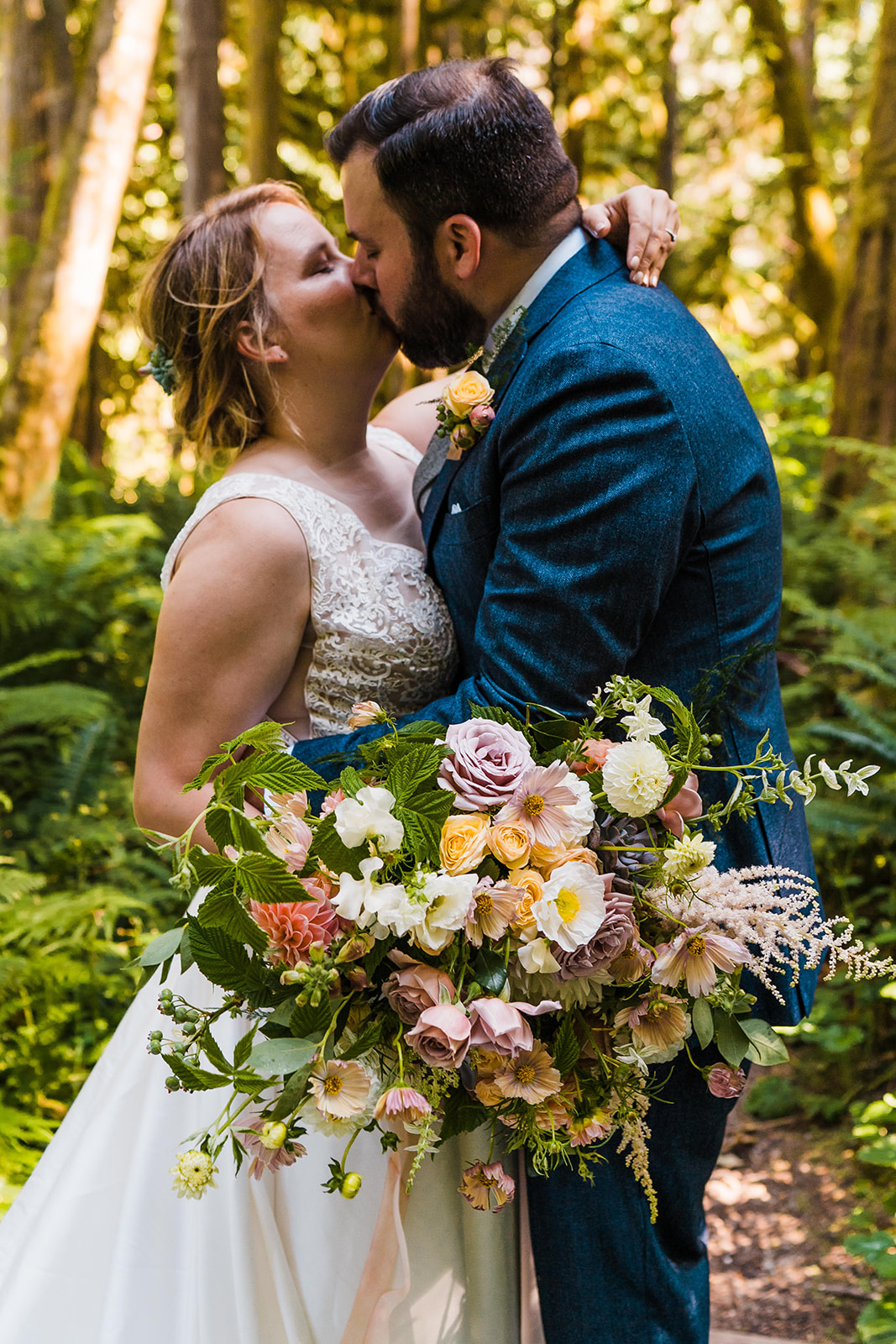 A couple kissing and holding a summer bridal bouquet full of vibrant summer flowers in peach and mauve tones
