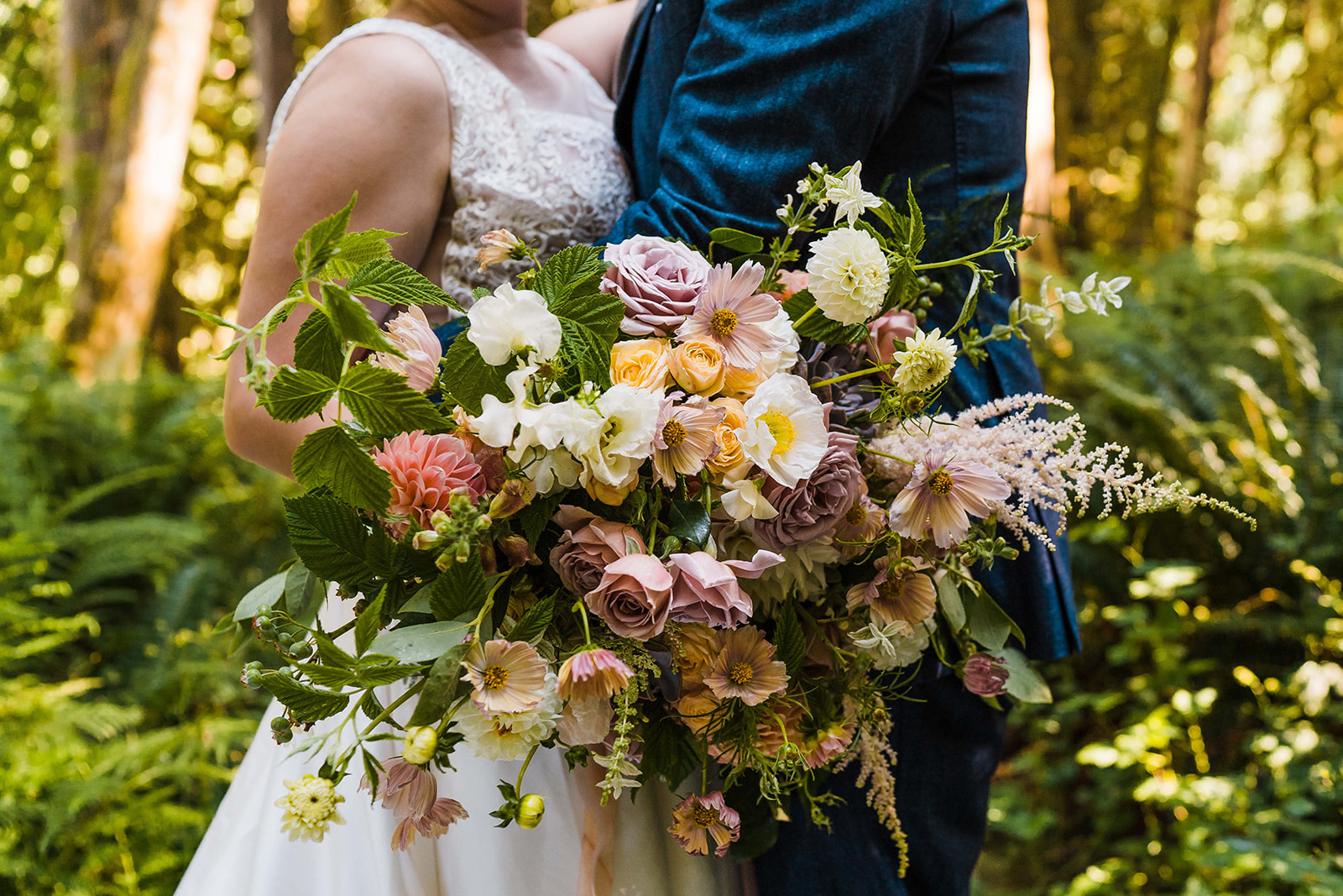 a bridal bouquet full of garden roses, poppies, cosmos, astilbe, dahlias, and raspberry and blueberry greens