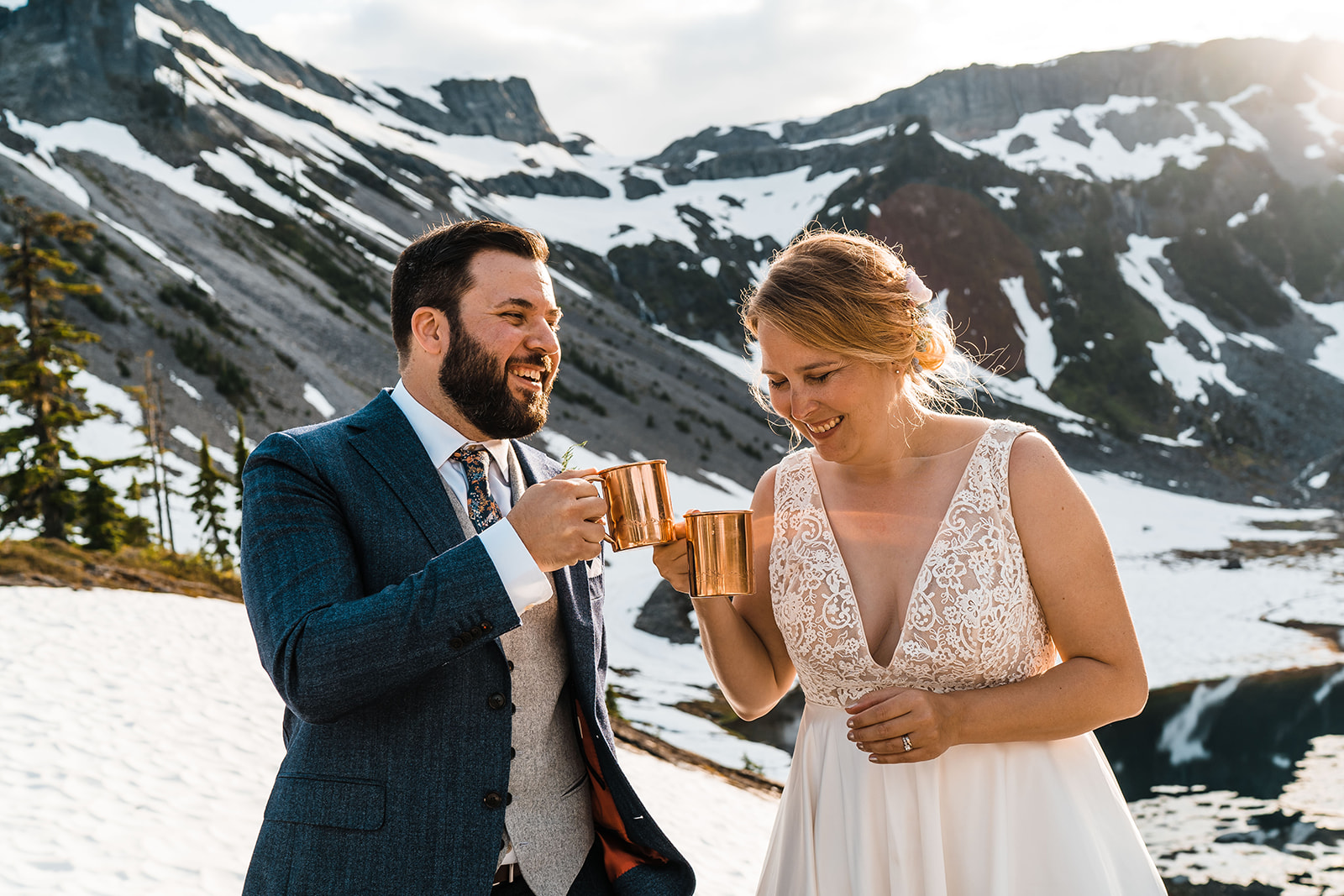 bride and groom on mountaintop with copper mugs smiling