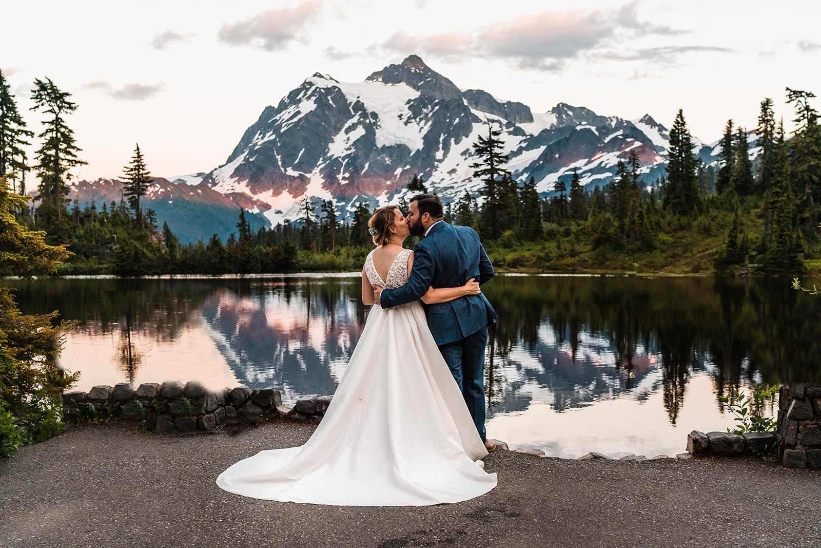 Couple hugging in front of mountain lake at sunset elopement