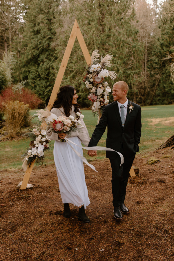 Couple eloping at Cedar Meadows in Bellinghamn in front of a triangle arch with a winter tropical floral design