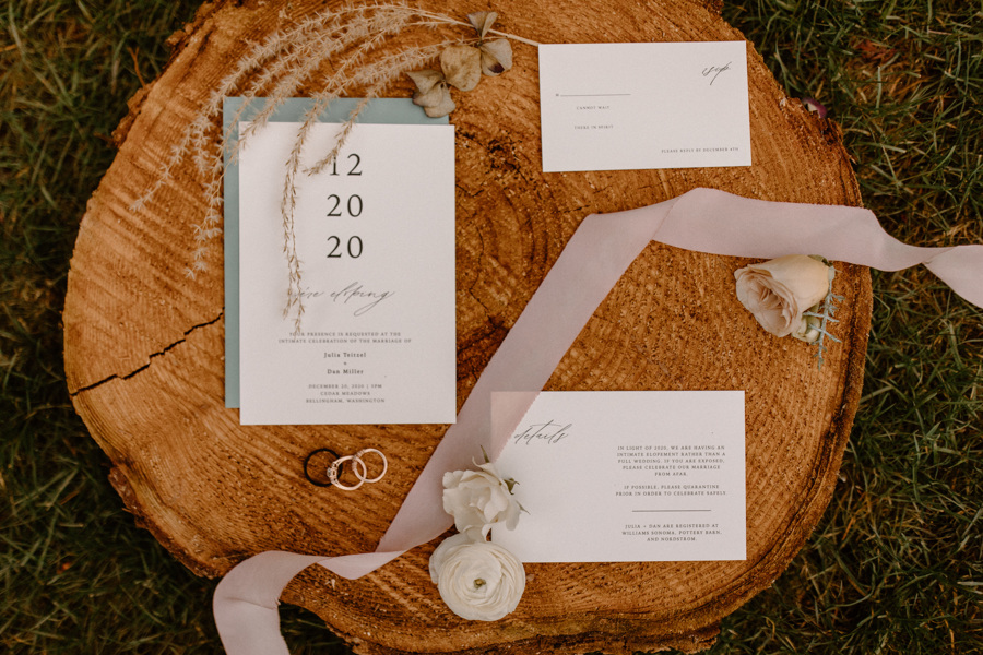 wedding invitation on wood round with ribbon and flowers