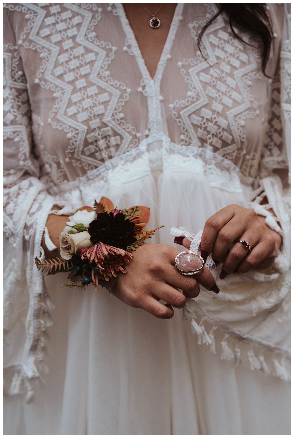 The bride with a fall flower cuff and a large rose quartz ring with her boho wedding dress