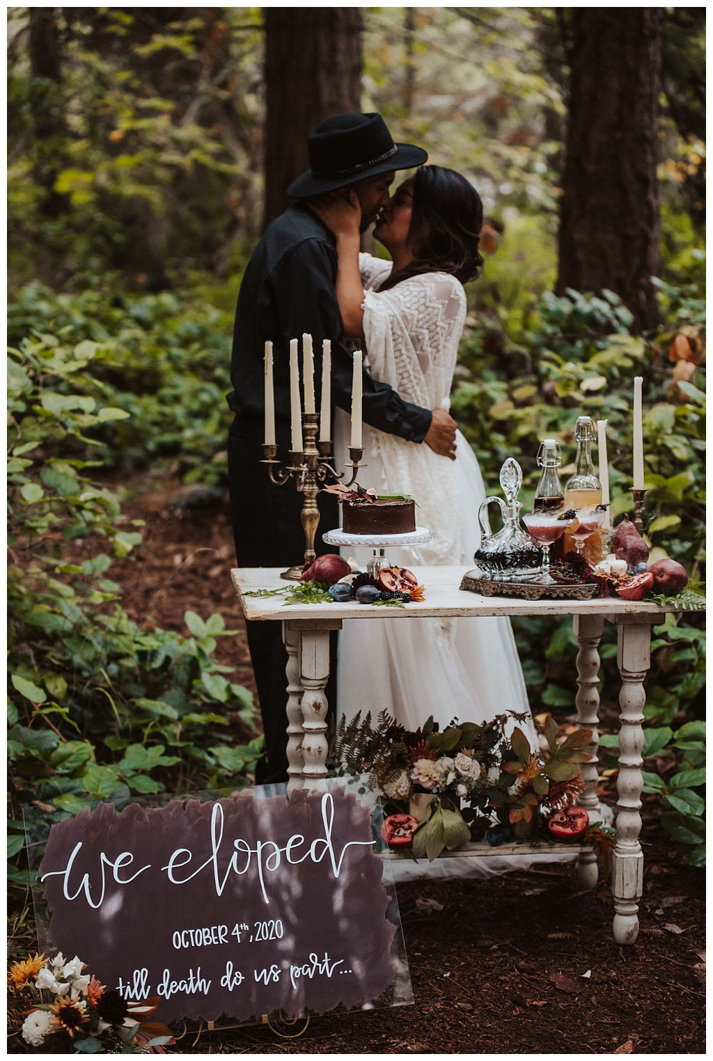 A vintage cocktail table in the woods for an elopement, with a cake, beverages, candles, and florals.