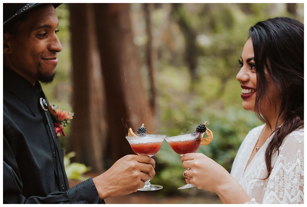 A multiracial couple toasting their Seattle elopement in the woods with bubbly blackberry cocktails
