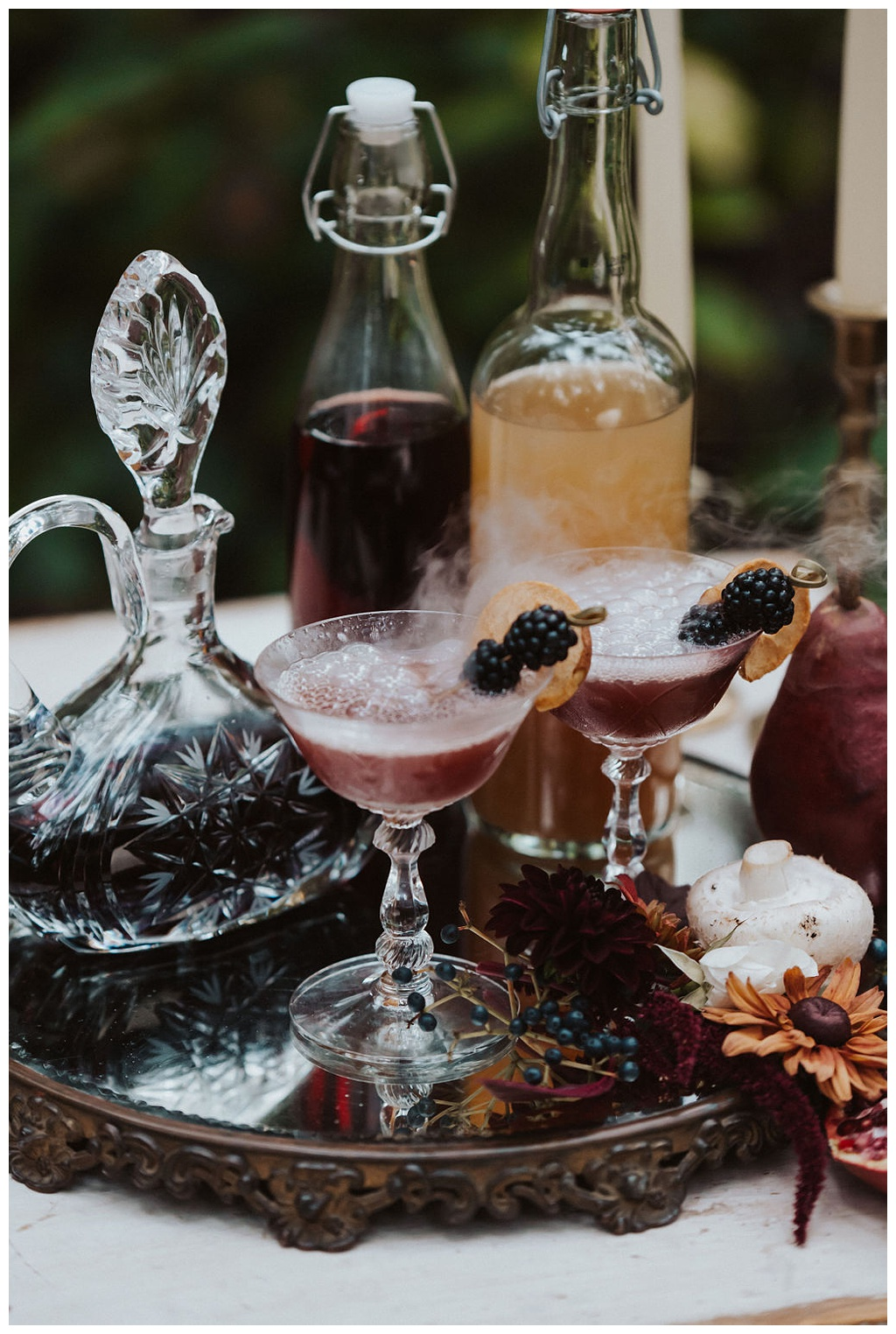 A table with cocktail goblets smoking with dry ice, as well as a vintage decanter and flowers and mushrooms.