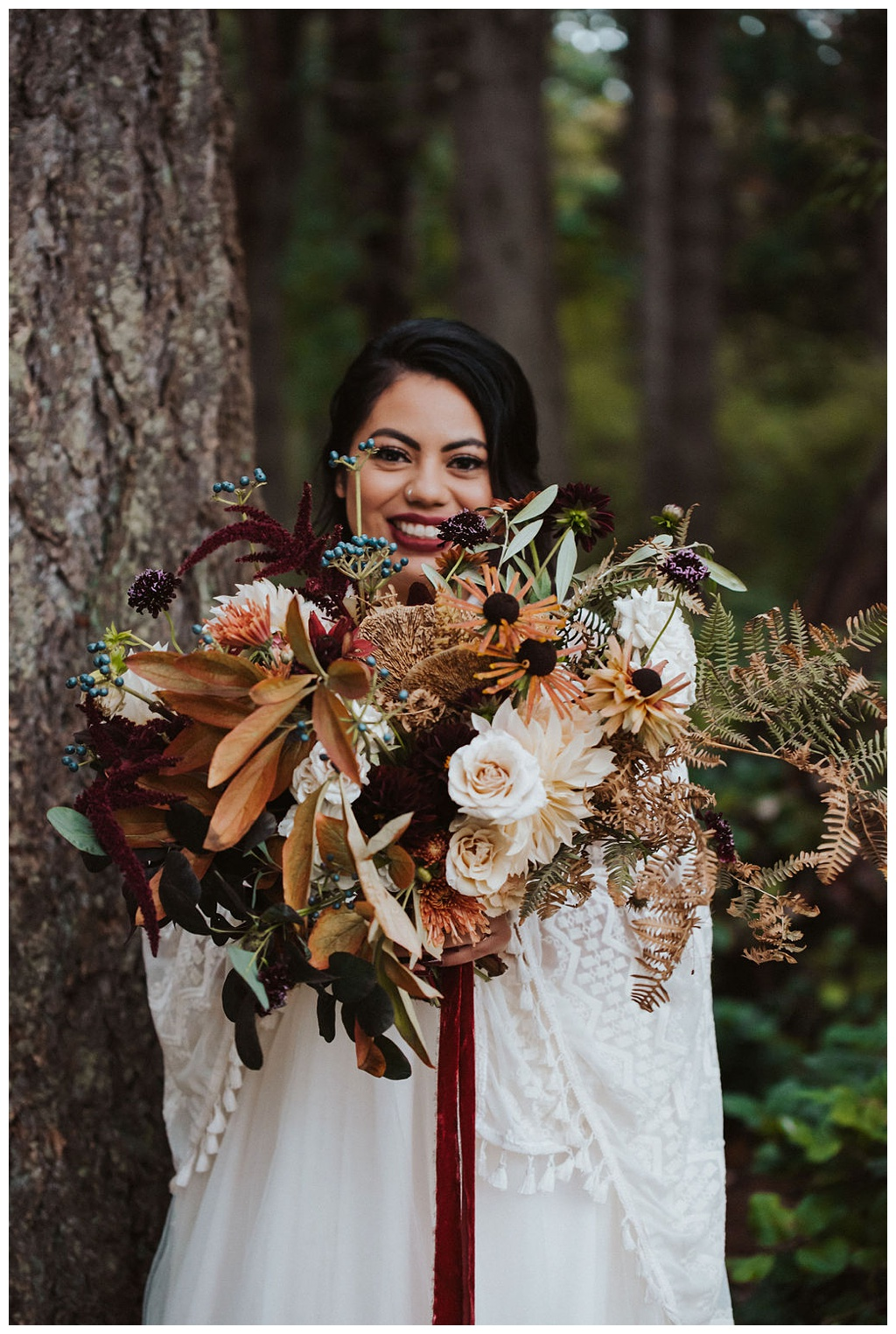 A bride holding her fall bouquet with roses, dahlias, and foraged foliage.