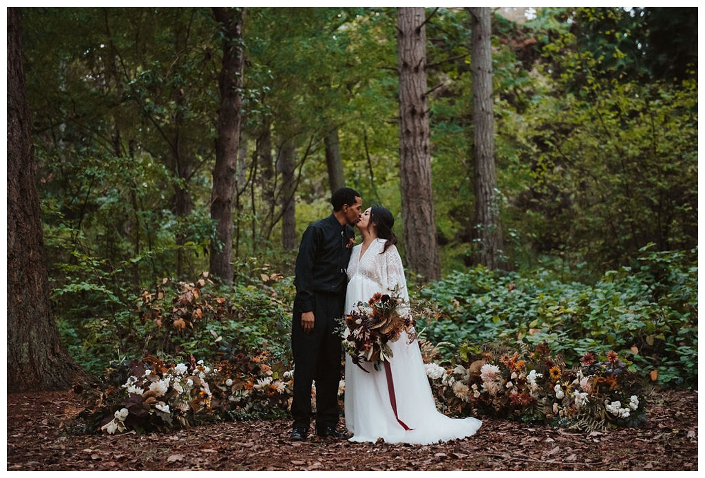 An interracial couple in the woods in front of a grounded flower arch, holding a bouquet and kissing