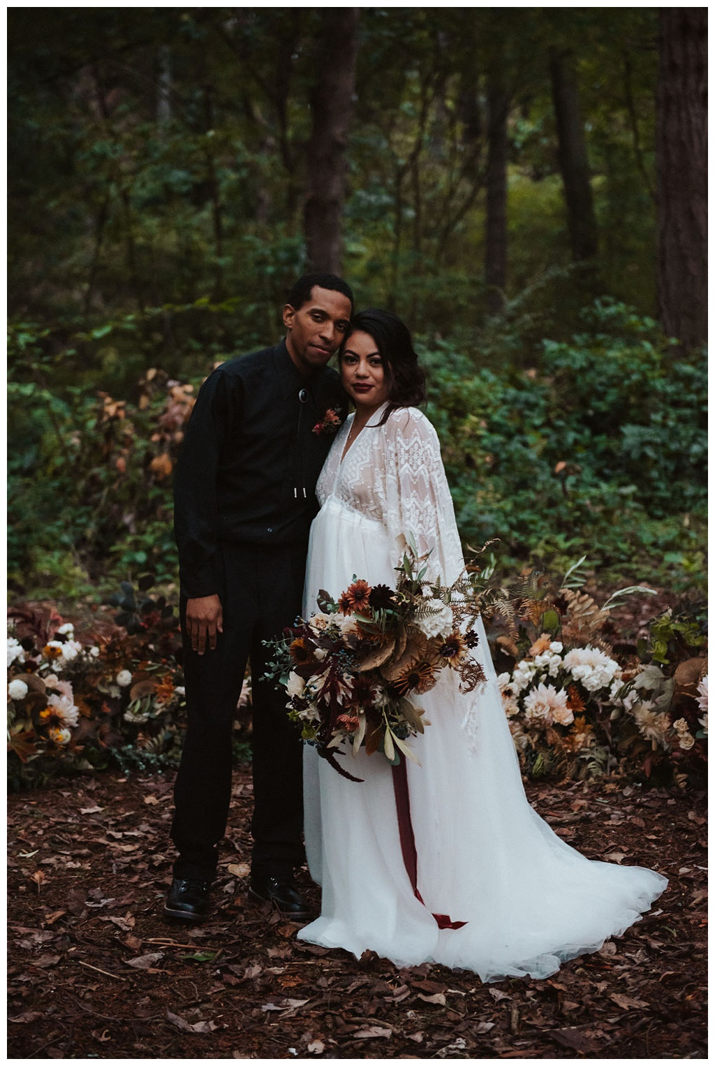 An interracial couple in front of their grounded arch for their woodland elopement, holding fall wedding bouquet