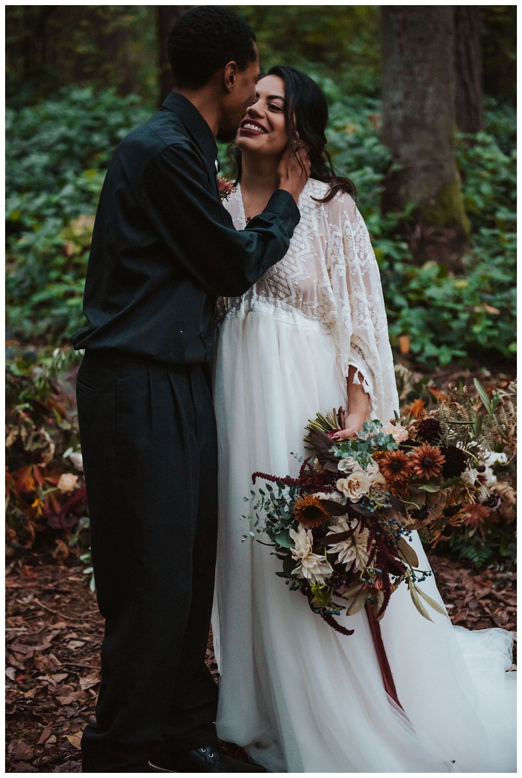 An interracial couple kissing during their wedding ceremony at a fall forest elopement in Seattle
