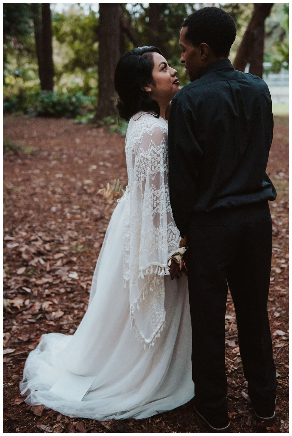 A wedded couple having a private moment in the woods after their elopement