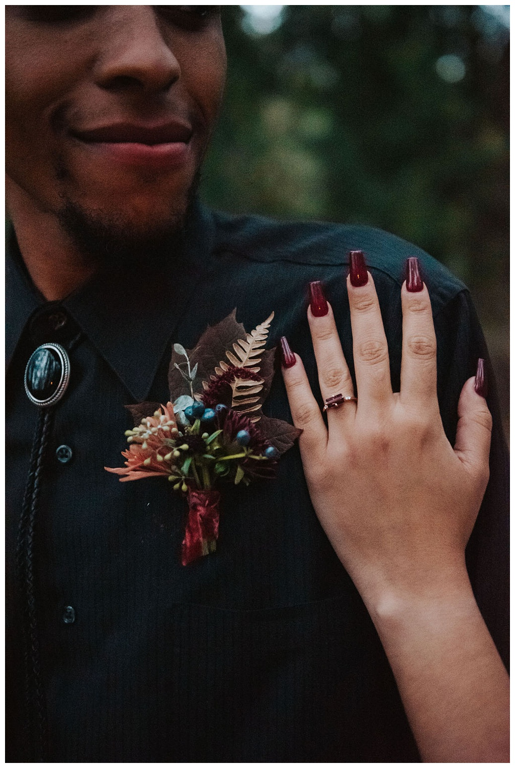 The groom with a boutonniere, and his wife's hand on his shoulder. The boutonniere is full of fall textures like berries, leaves, and dried fern