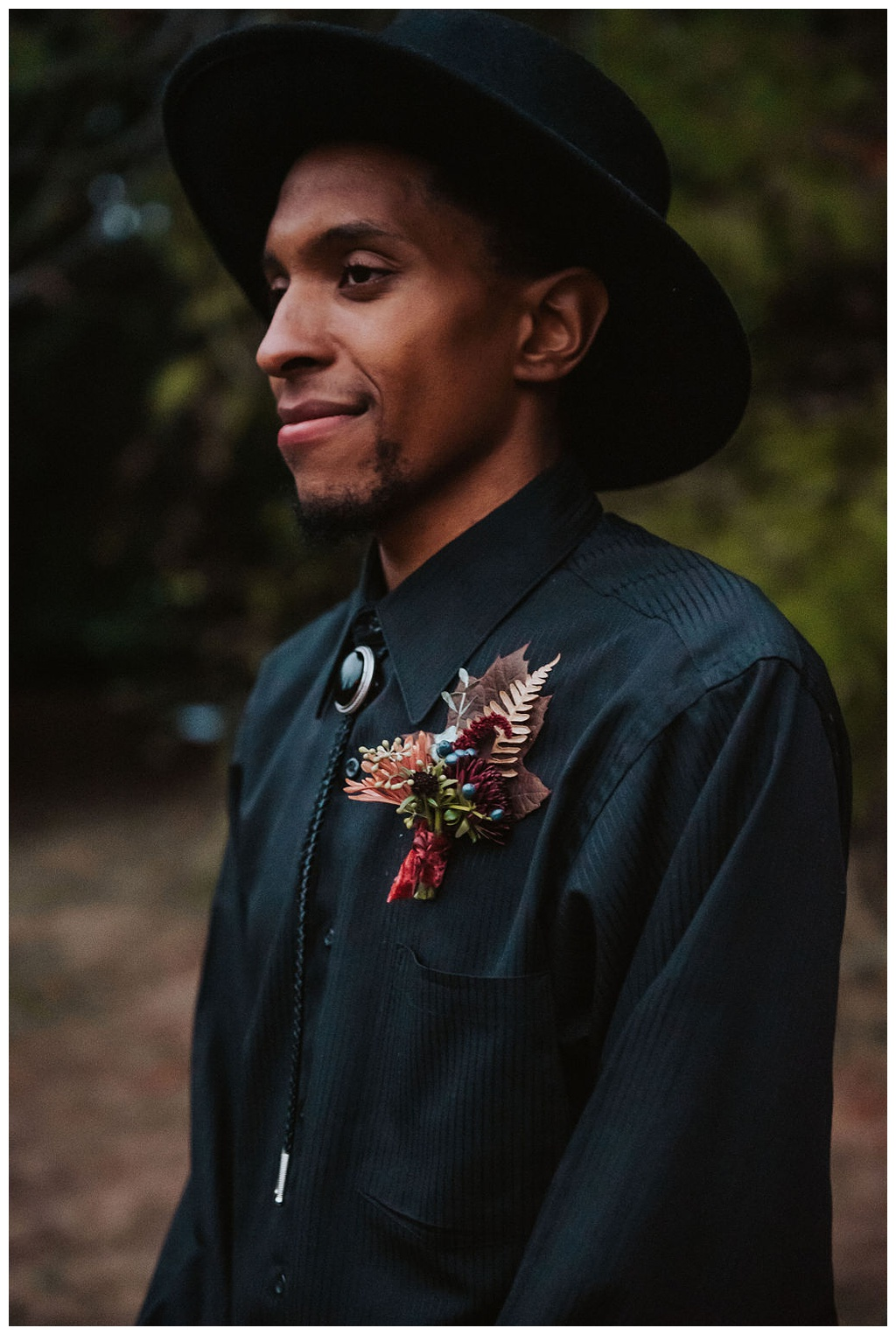 The groom looking away from his bride, with a black shirt, bolo tie, black hat, and fall boutonniere.
