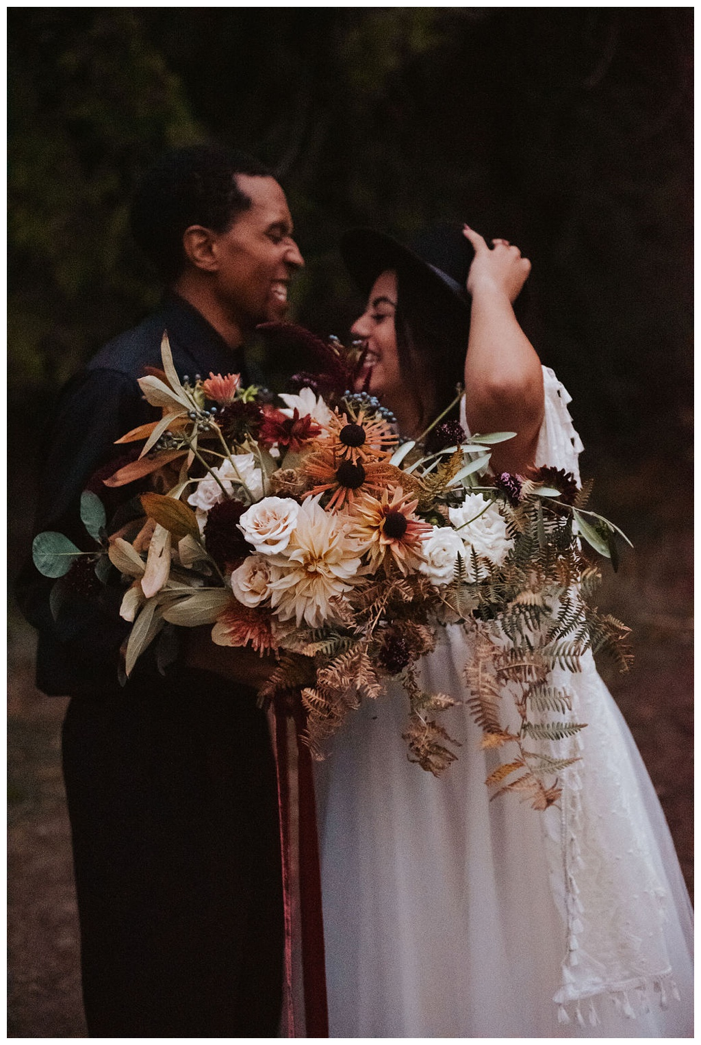 A couple smiling and laughing in the woods, holding a fall bridal bouquet