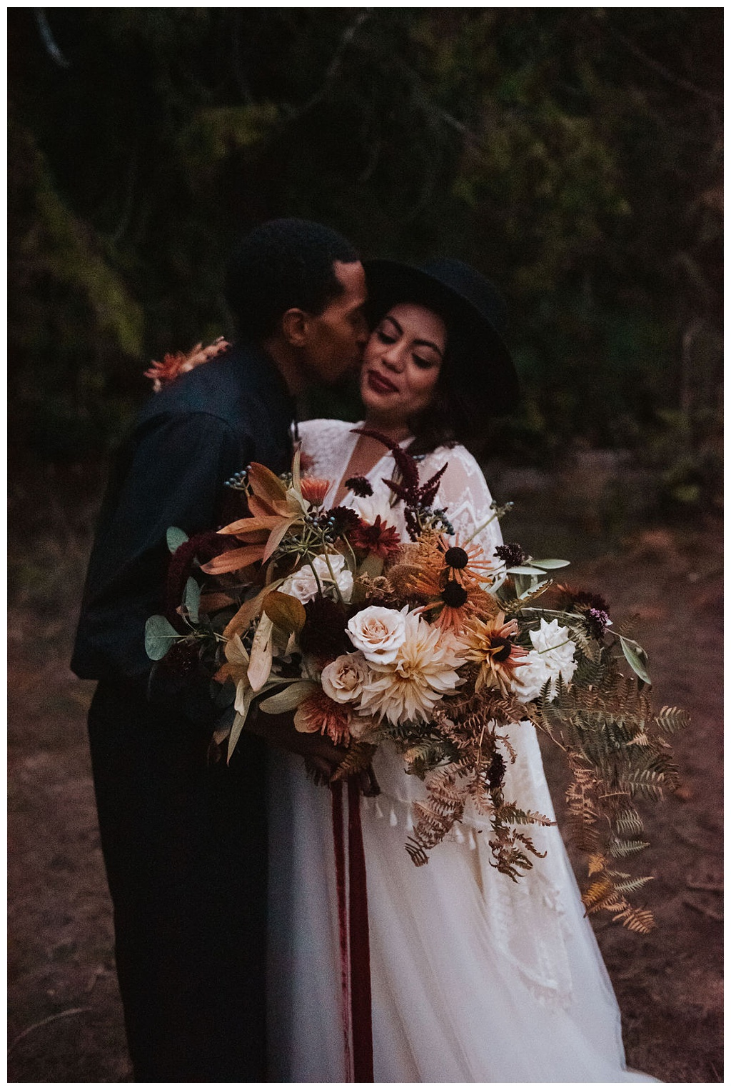 A couple in the woods, holding a bridal bouquet