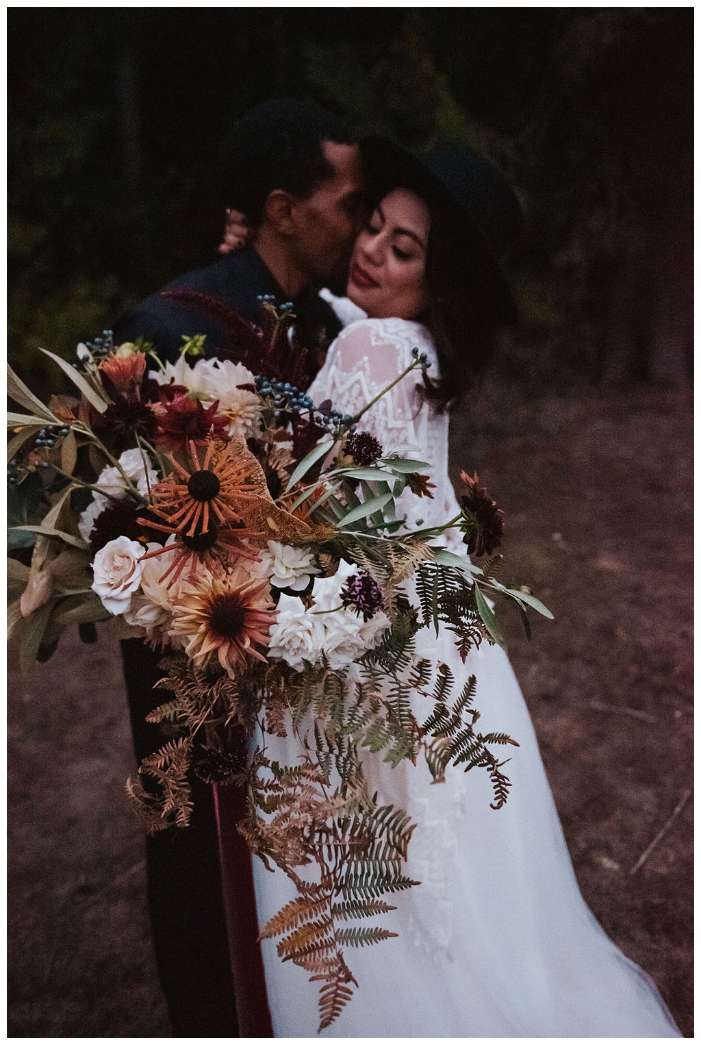 An interracial couple embracing in the woods with a fall bouquet