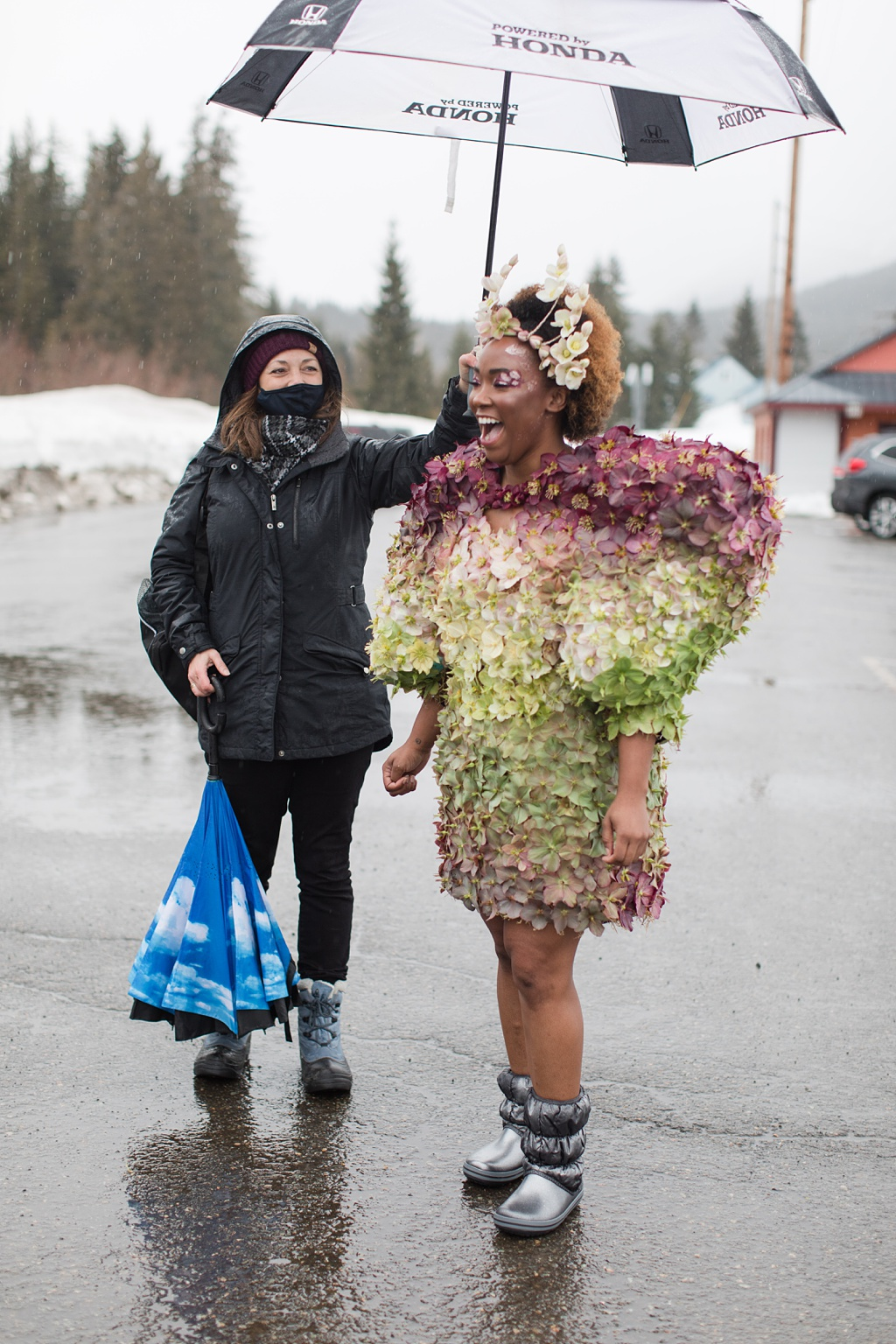 Pamela Youngsman holds an umbrella for model Tasia in the hellebore couture dress