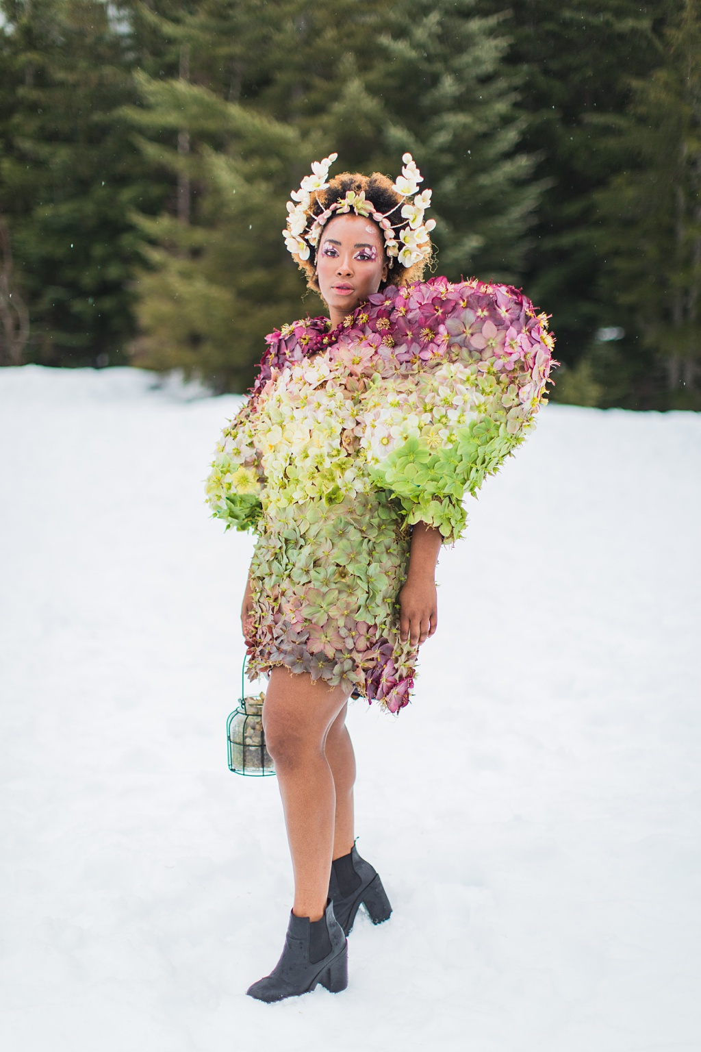 A woman in a dress made of hellebores with a crown made of hellebores in the snow, holding a lantern