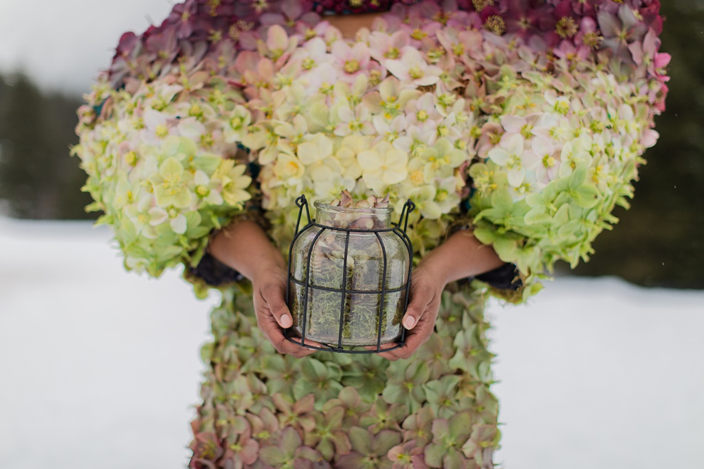 a model holding a lantern in front of the ombre couture hellebore dress