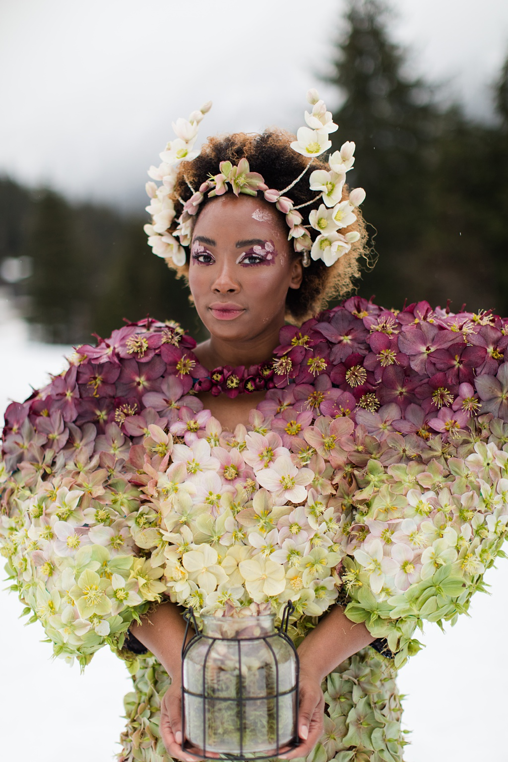 A woman in a dress made of hellebores with a crown made of hellebores in the snow