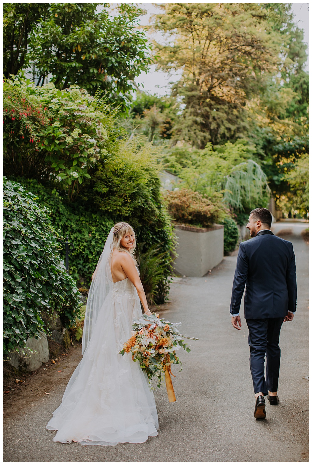 a bride looking behind her shoulder, surrounded by landscaping, holding a bridal bouquet while her groom walks ahead