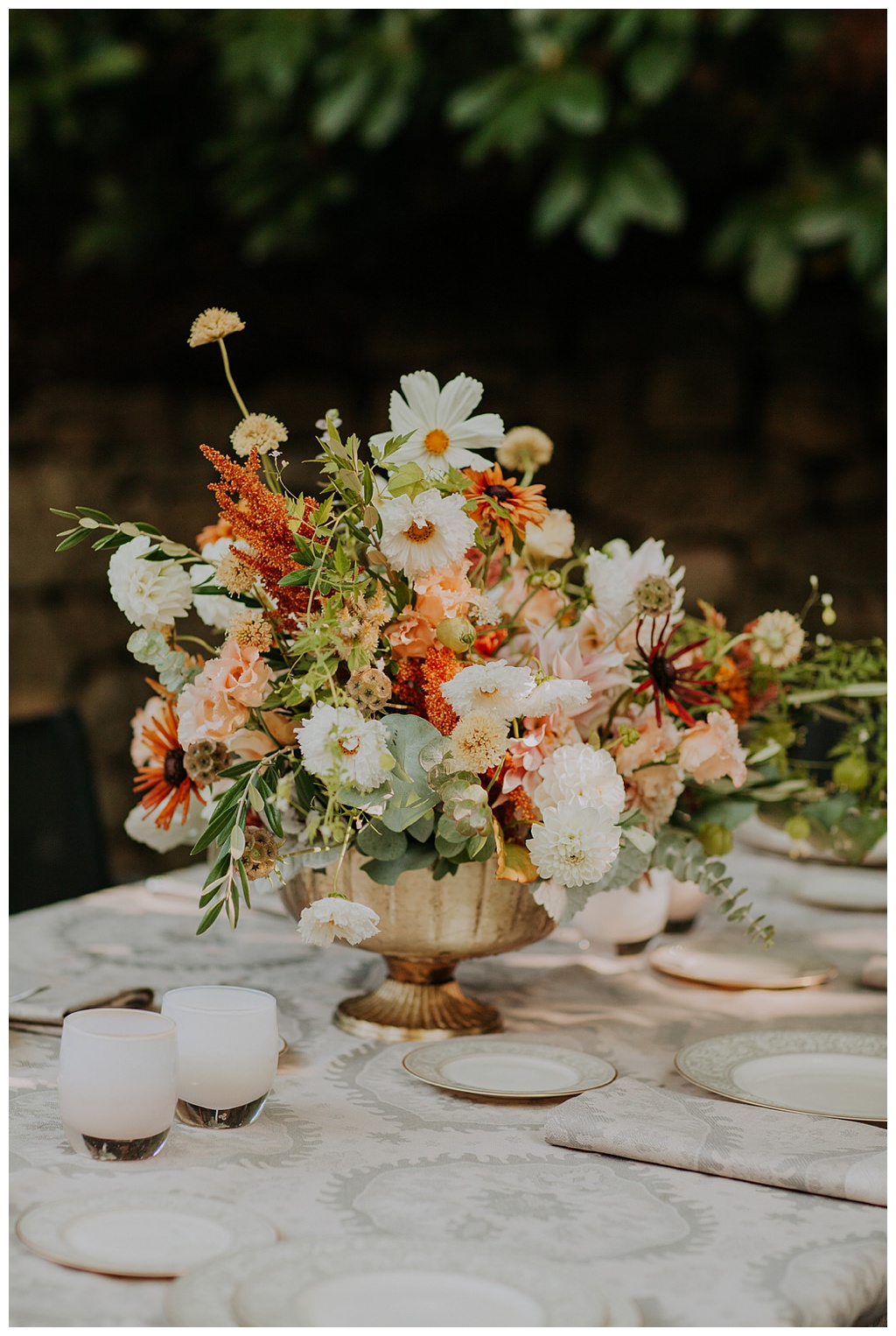 an outdoor wedding table with fine china, antique silver, and a boho floral centerpiece full of neutral and earthy flowers