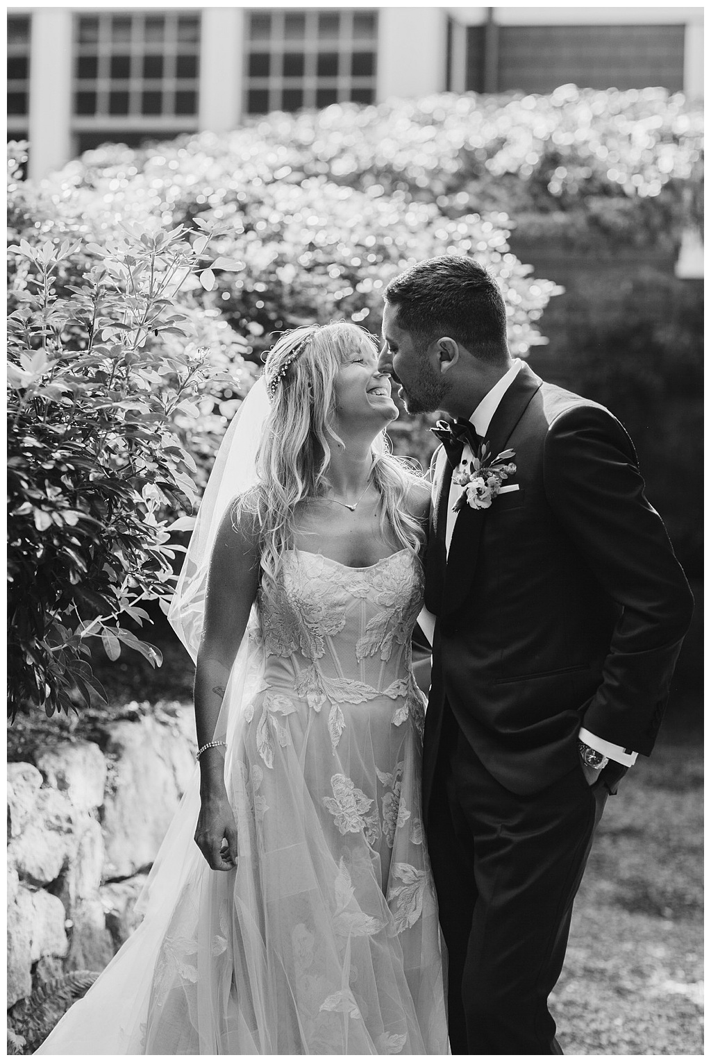 a black and white image of the bride and groom kissing in the garden