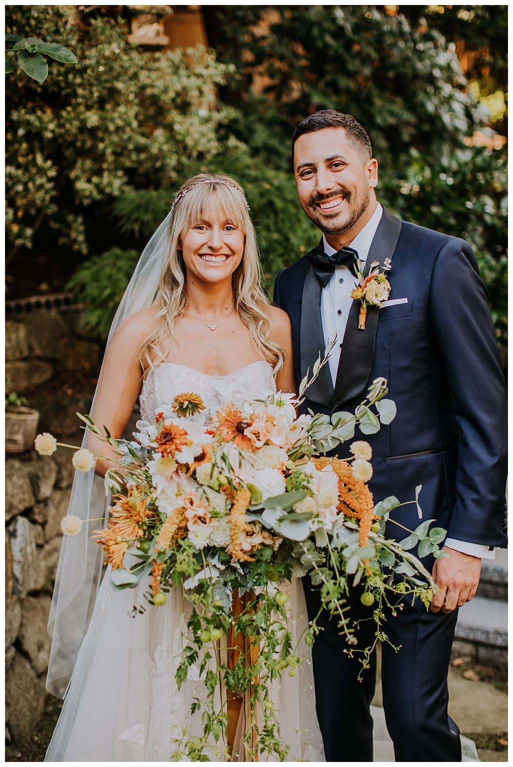 the happy couple with a bridal bouquet of dahlias, eucalyptus, love-in-a-puff, lisianthius, celosia, scabiosa, rudbeckia, and other local and seasonal flowers