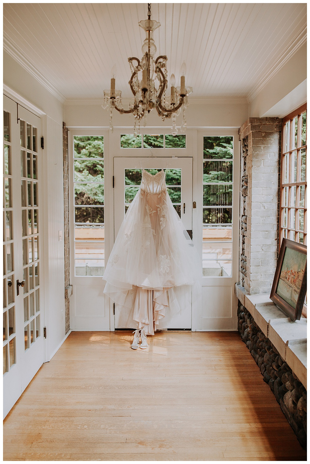 a wedding dress hanging from the window in a greenhouse room with a chandelier