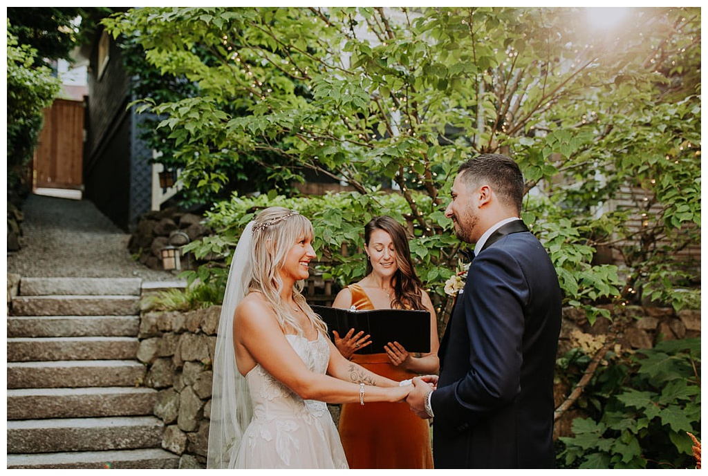 a bride and groom holding hands while the officiant reads from a book