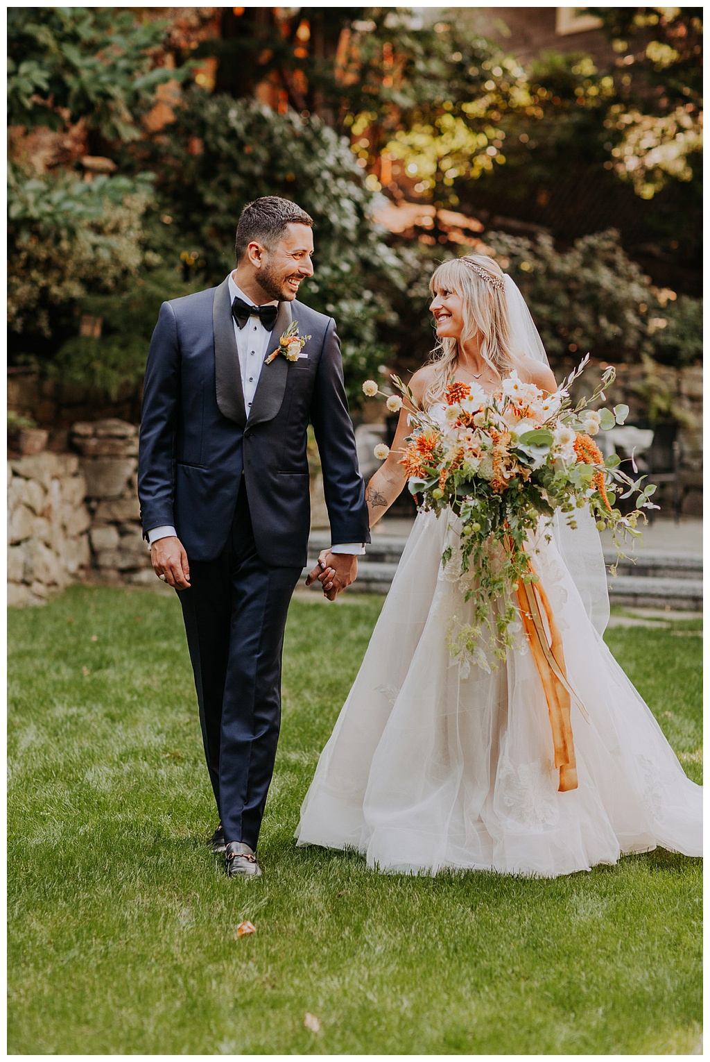 a bride and groom holding hands, walking across grass, bride holding a bouquet of wedding flowers with long silk ribbon