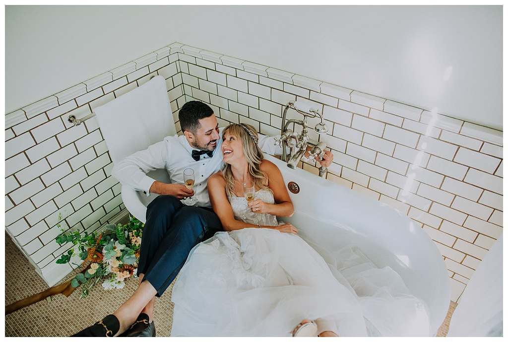 a wedding couple lounging in a clawfoot bathtub, holding champagne flutes and laughing
