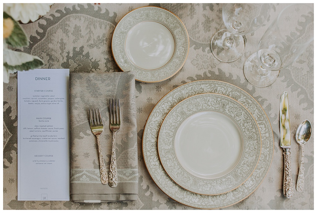 an elegant table setting with fine china with grey rim, antique silver, and patterned tablecloth with printed menu