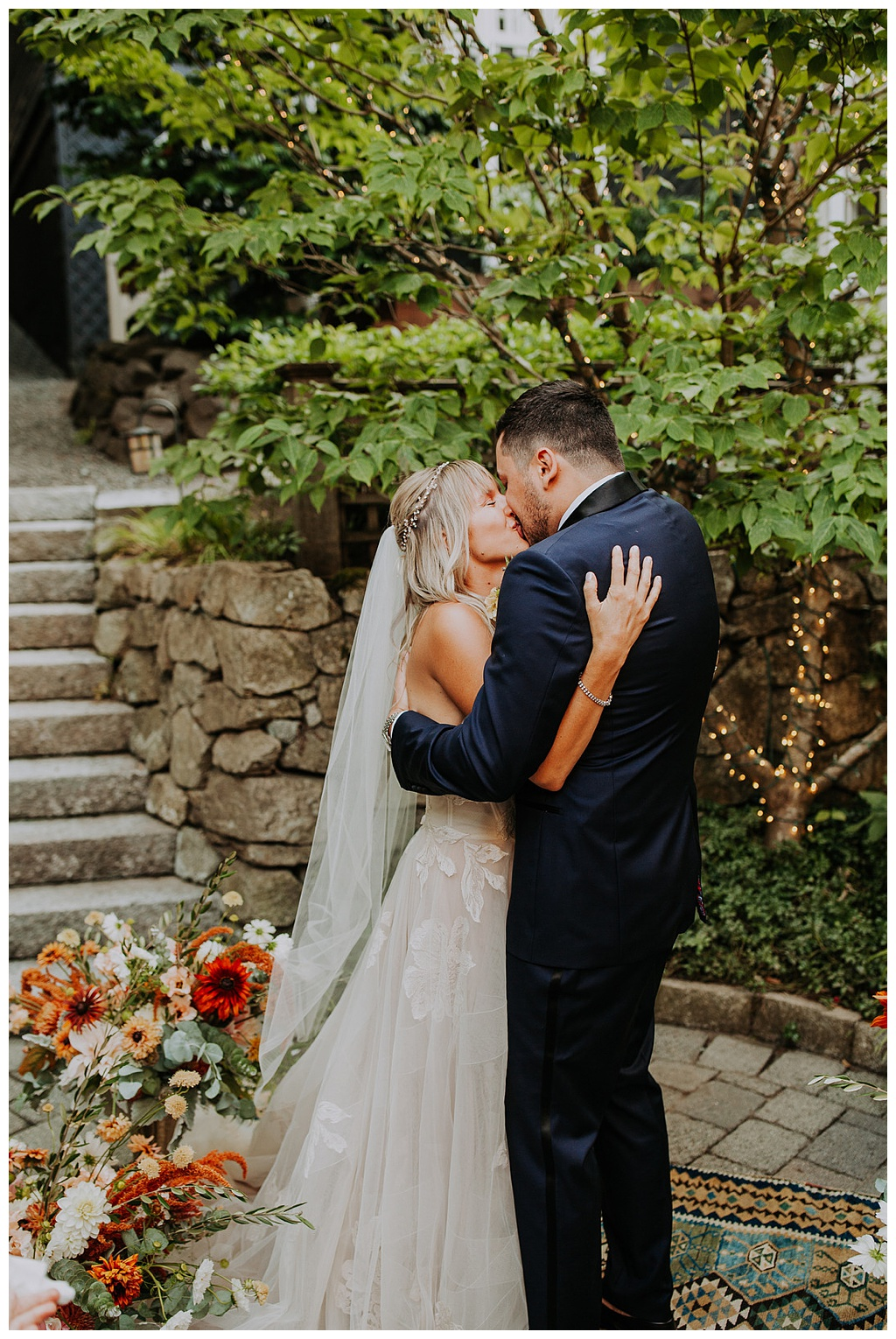 the couple embraces during the ceremony, with the boho floral arrangements in the foreground