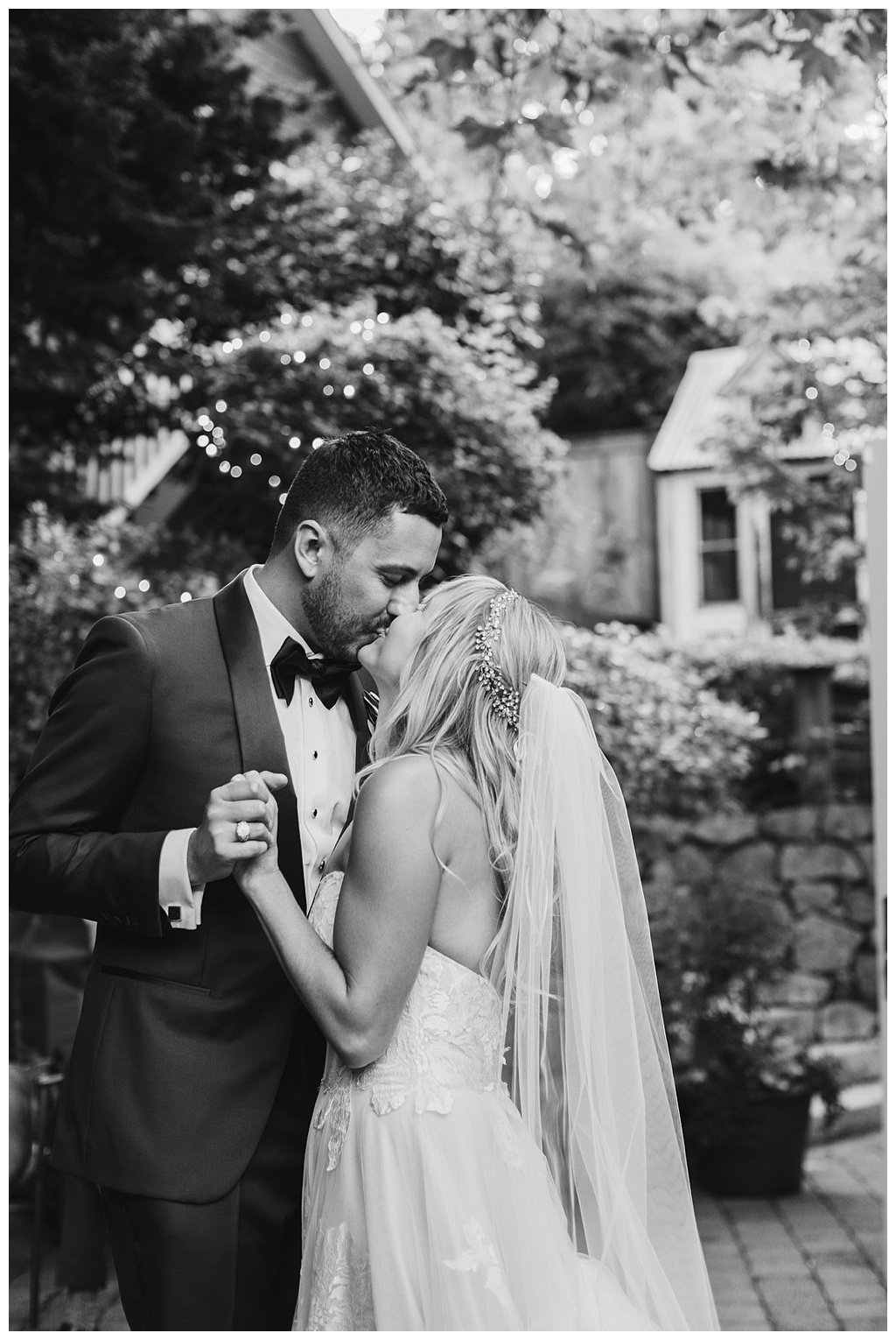 a black and white image of a couple kissing at their outdoor wedding in Seattle