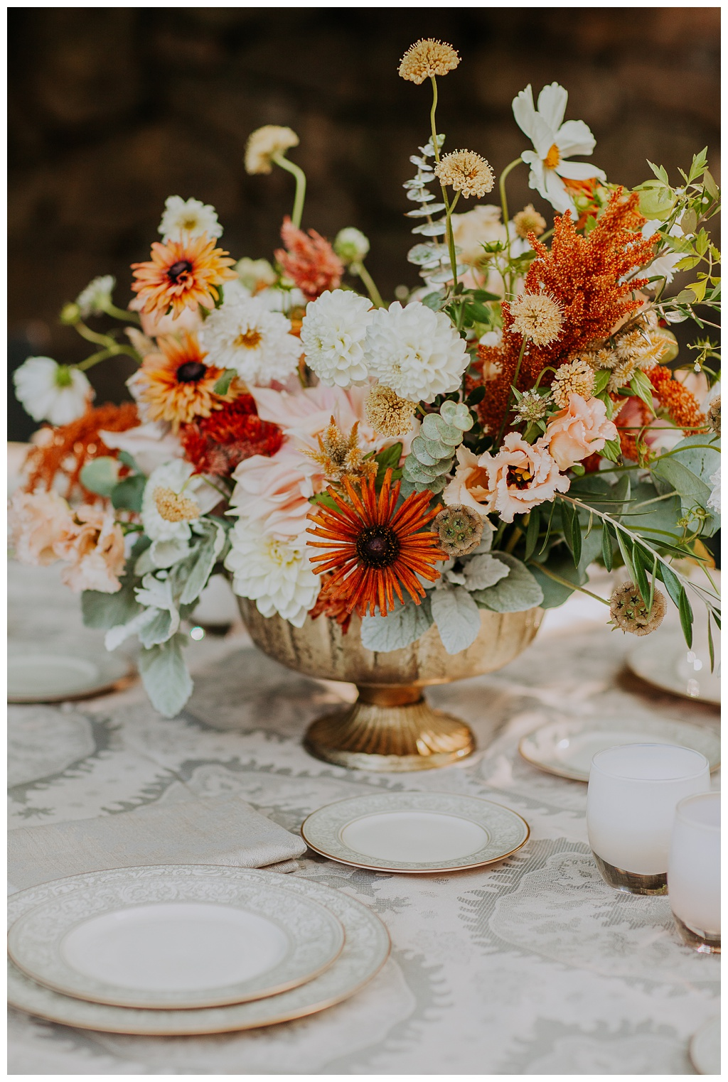 a wedding flower centerpiece on a table with fine china and dahlias, cosmos, lisianthius, and rudbeckia