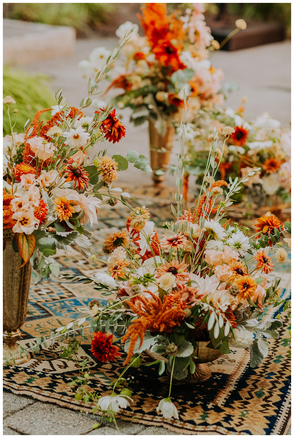 boho wedding ceremony with vintage rug and large floral urns to create an altar