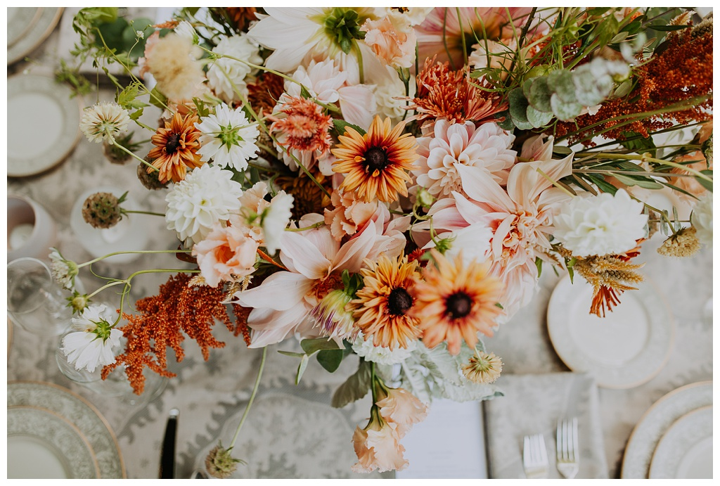 an overhead shot of a table with boho wedding flowers