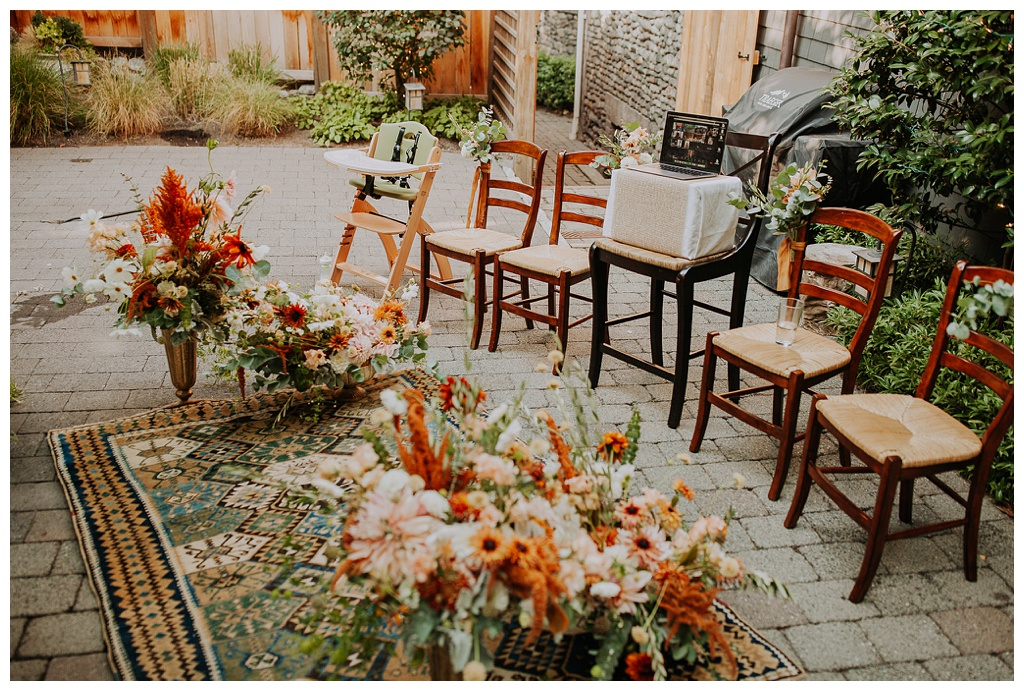 an outdoor wedding ceremony setup during covid, with five chairs and a table for streaming the wedding to family