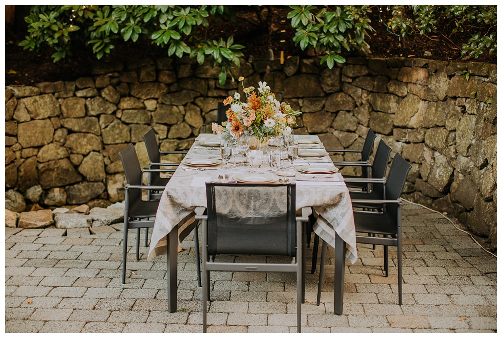 an outdoor wedding reception table on a stone patio with lush boho floral arrangements, fine china, and grey linens