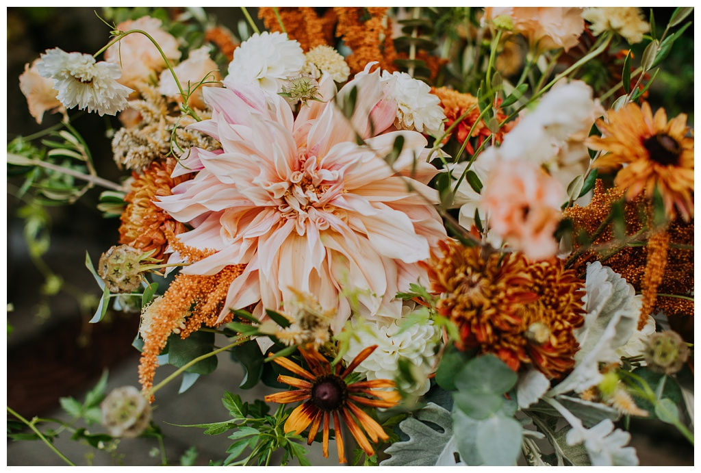a boho wedding flower centerpiece with cafe au lait dahlias, rudbeckia, eucalyptus, and amaranth