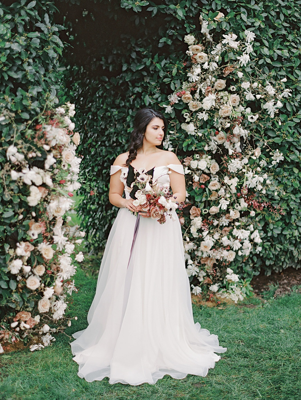 """A bride holding a bouquet stands in front of a manicured hedge """"doorway"""" to the vineyard at Chateau Lill"""
