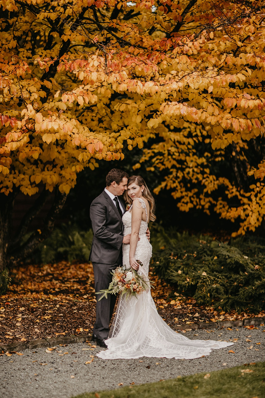 a bride and groom standing under a tree with bright yellow fall leaves