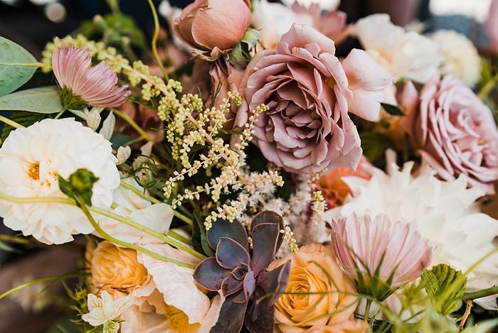 a closeup of the summer wedding flowers including astilbe, garden roses, dahlias, and cosmos