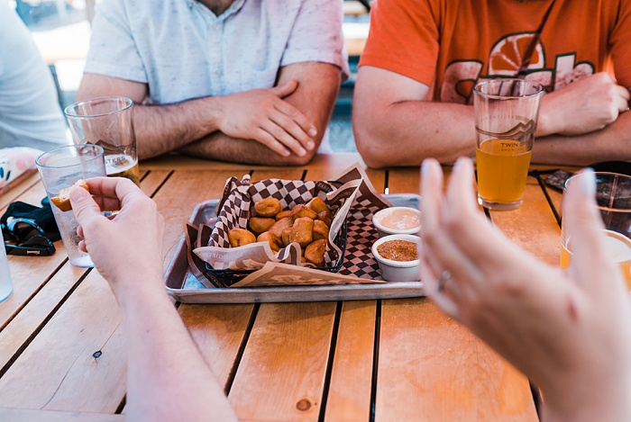 a family having a casual lunch at a brewery picnic table