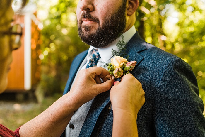 a mom helping a man pin a boutonniere for his wedding day